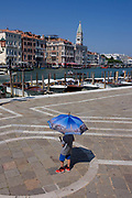 A boy carries a Venice picture umbrella in front of Santa Maria della Salute church in the Dorsoduro district, overlooking the Grand Canal and San Marco. This is the heart of Venice and where, for most daylight hours, the pavements are crowded wih humanity as the influx of tourists who, in their own way, flood the narrow streets with sun-shading umbrellas and the smaller canals with gondolas.