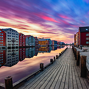 "website: www.azinasutiphotography.com      Ver special colors on Trondheim on 28 May 2018. I was very surprised to see such a strange but beautiful colors in the sky.         At Nidelva's outlet there have been seaside stalls, breweries and warehouses all the way from the oldest times. Here the towners traded with goods from far and near.<br /> <br /> At the time of King Sverres, the bridges were also used as defense works. Towards the river, screens and times were built. From here you could throw stones on the enemy. In Magnus Lagabøte's city council of 1276, it is stated that the swallow, a passageway outside the bridges, should not be wider than three ales; further that between the brews should be ""droplet"" distance. The brewery that is still preserved is located on both sides of Nidelva - in Kjøpmannsgata, in Bakklandet, in Fjordgata and Sandgata. The oldest preserved breweries are from the mid-18th century."