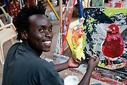Rwanda February 2014. Kigali. Inema Arts Centre. Artist Timothy Wandulu painting a robin. Two years after the genocide , a vibrant artistic community is emerging in Rwanda .