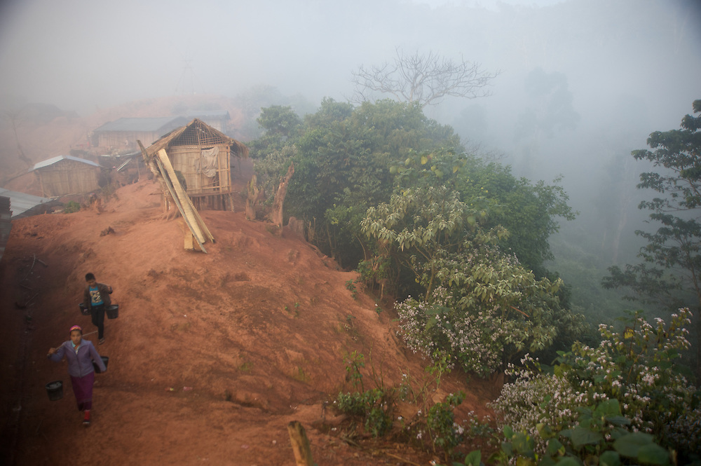 Villagers carry water through a remote village in northern Laos.