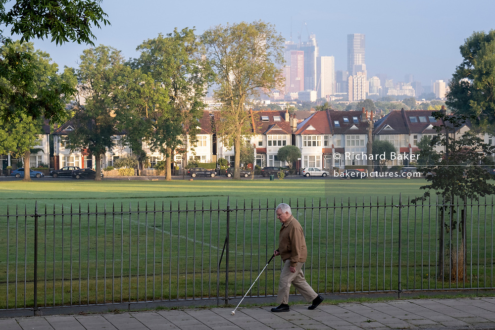 An unsighted man walks alongside park railings with a background of Edwardian period homes bordering Ruskin Park in south London with residential high-rises at the distant Nine Elms development in Battersea, on 16th September 2021, in London, England.