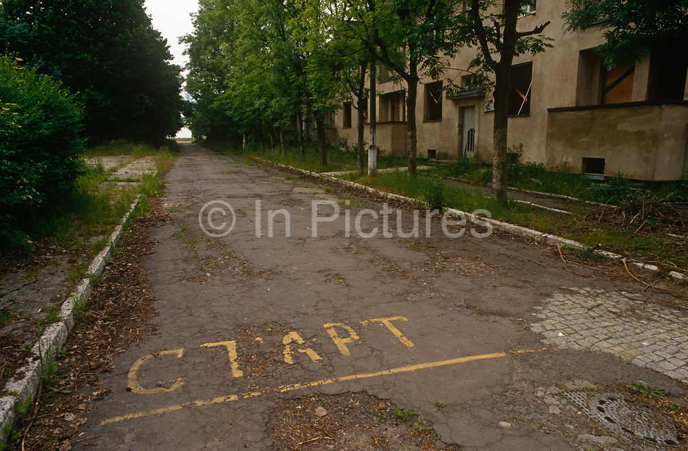 A deserted landscape of a street and overgrown paths and empty housing in the former Russian Soviet army camp in occupied East Germany ex-GDR/DDR, on 16th June 19990, on Halb Insel Wustrow, near Rostock, Germany. Wustrow was once a WW2 German anti-aircraft artillery position then housing civilian refugees before the eventual Soviet occupation of the former DDR during the Cold War, up until 1990 and the fall of communism and the Berlin Wall. The camp was ransacked and all its assets stripped before its desertion that summer and is a reminder of a fallen ideology.