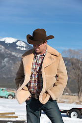 cowboy in a shearing coat near snow covered mountains