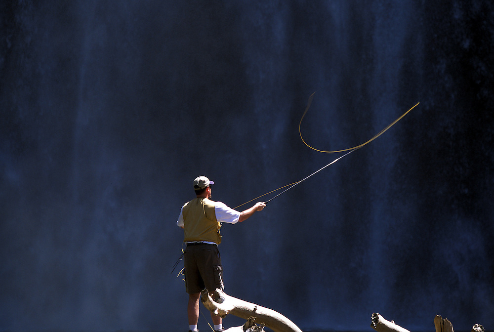 A man fly fishes at Rainbow Falls, located in Reds Meadow, part of the Ansel Adams Wilderness, in Mammoth Lakes, CA.