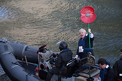 © licensed to London News Pictures. London, UK 30/10/2012. Boris Johnson arriving to HMS Severn on a poppy branded RIB and holding big poppy sign to launch London Poppy Day with the captain and crew of HMS Severn in Canary Wharf. Photo credit: Tolga Akmen/LNP
