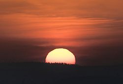 © Licensed to London News Pictures. 13/02/2017. Guildford, UK.  The sun rises over trees viewed from Newlands Corner near Guildford.  Sunshine and warmer temperatures are expected in the south today after the recent cold spell.  Photo credit: Peter Macdiarmid/LNP