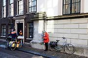 In Dordrecht praten twee postbestellers van PostNL met een oudere vrouw op de fiets.<br /> <br /> In Dordrecht two mailmen talk to an elderly woman on a bike.