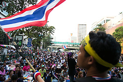 © Licensed to London News Pictures. 05/01/2014. An Anti Government protester waves the Thai Flag in front of a large group of Anti Government supporters during the third day of the 'Bangkok Shutdown' as anti-government protesters continue with their 'shutdown' of Bangkok.  Major intersections in the heart of the city have been blocked in their campaign to oust Prime Minister Yingluck Shinawatra and her government in Bangkok, Thailand. Photo credit : Asanka Brendon Ratnayake/LNP