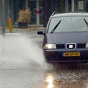 NLD/Huizen/20050704 - Ondergelopen straten na zware regenbuien, auto door plassen