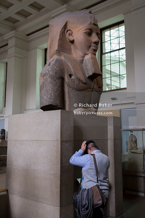 The colossal head of ancient Egyptian Pharaoh Ramses II that dominates a room and visitors in the British Museum, on 28th February 2017, in London, England.