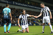 Jonas Olsson of West Bromwich Albion is helped up on his feet by Chris Brunt of West Bromwich Albion.  Premier league match, West Bromwich Albion v Swansea city at the Hawthorns stadium in West Bromwich, Midlands on Wednesday 14th December 2016. pic by Andrew Orchard, Andrew Orchard sports photography.