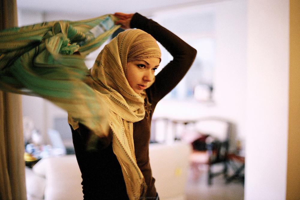 Jeune femme musulmane essayant différentes combinaisons de hijab chez elle, France 2006. <br /> Muslim woman trying multiple combination of hijab at home, France 2006.