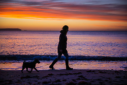 © Licensed to London News Pictures. 01/12/2020. Mudeford, UK. A woman walks her dog on the sea front at Mudeford in Dorset as the winter sun illuminates the clouds above The Isle of Wight (L). Most of England is experiencing low temperatures and clear skies today on the first day of the Meteorological winter. Photo credit: Peter Macdiarmid/LNP