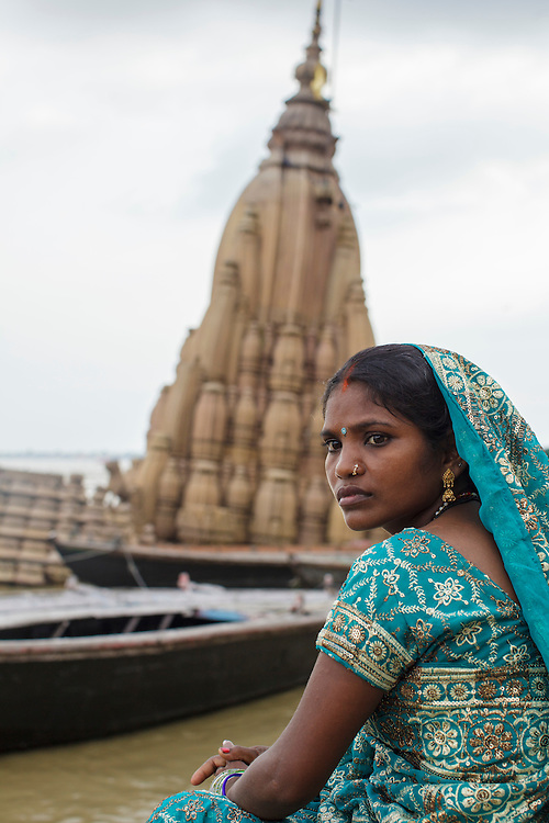 Young hindu woman near a sunken temple at Dattatreya Ghat, by the Ganges river, in Varanasi, India.