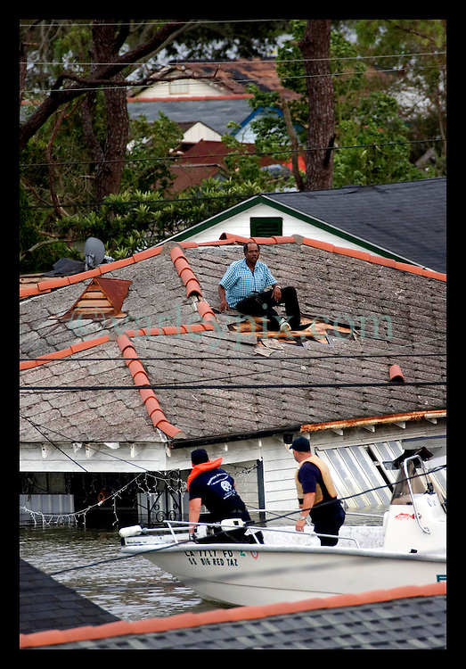 29th August, 2005. Hurricane Katrina hits New Orleans, Louisiana. Rescuers collect Arthur White who smashed his way out of his attic when he became  trapped in his house in the lower 9th ward as it disappeared under water.
