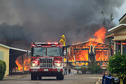 July 6, 2018 - Alpine, California, U.S. - Firefighters wait for water as they battle flames at the Alpine Oaks Estates mobile home park on Friday during a fire in Alpine amid a dangerous heat wave. A fast-moving brush fire in Alpine burned 400 acres, destroyed several structures and prompted evacuations. (Credit Image: © Eduardo Contreras/San Diego Union-Tribune via ZUMA Wire)