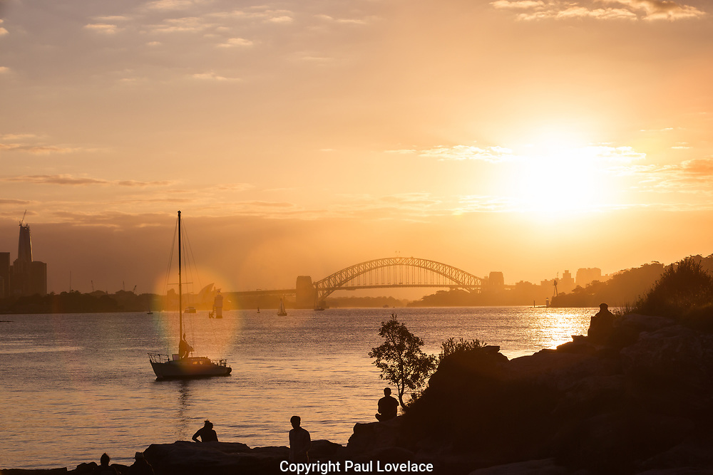 Lens flare and silhouettes of  people admiring the view of Sydney Harbour on Milk Beach just before sunset, Sydney Harbour National Park, Vaucluse, Sydney, Australia.