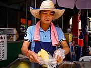 29 JUNE 2018 - BANGKOK, THAILAND: A fruit vender on Soi Wanit 2 near the Chao Phraya River in Bangkok's Chinatown prepares an order of sliced pineapple for a customer.     PHOTO BY JACK KURTZ