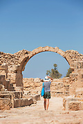 Tourist walking by arch in Paphos Archaeological Park in Cyprus