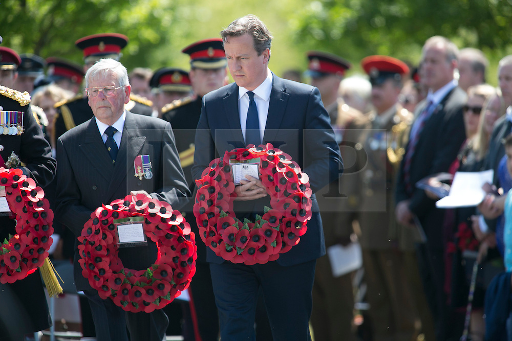 © Licensed to London News Pictures. 11/06/2015. National Memorial Arboretum, Alrewas, Staffordshire, UK. The service to mark the Rededication of the Bastion Memorial. The memorial was begun in Helmand Province in 2006, deconstructed in 2014 and now replicated at the National Memorial Arboretum in Staffordshire. Around two thousand people took part in the service including HRH Prince Harry, the Prime Minister David Cameron and senior members of the Armed Forces. Pictured, DAVID CAMERON laying his wreath. Photo credit : Dave Warren/LNP