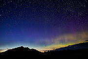 The northern lights or aurora borealis faintly shine over the North Cascades of Washington state as the twilight colors fade from the sky.