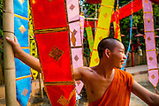 10 APRIL 2013 - CHIANG MAI, CHIANG MAI, THAILAND:  A monk hangs prayer flags for Songrkran in Wat Phan Tao in Chiang Mai. Songkran is celebrated in Thailand as the traditional New Year's Day from 13 to 16 April. The date of the festival was originally set by astrological calculation, but it is now fixed. Songkran is in the hottest time of the year in Thailand, at the end of the dry season, and provides an excuse for people to cool off in friendly water fights that take place throughout the country. The traditional Thai New Year has been a national holiday since 1940, when Thailand moved the first day of the year to January 1. The first day of the holiday period is generally the most devout and many people go to temples to make merit and offer prayers for the new year.    PHOTO BY JACK KURTZ