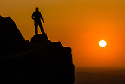 © Licensed to London News Pictures. 17/09/2020. Ilkley UK. A man watches the sun as it rises over the Cow & Calf rocks on Ilkley moor this morning in Yorkshire. Photo credit: Andrew McCaren/LNP