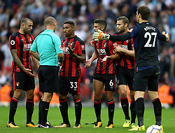 AFC Bournemouth's Jordon Ibe (centre right) talks to the Match referee Robert Madley (left)