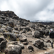 The rocky path through the apline desert on Mt Kilimanjaro Lemosho Route. These shots were taken on the trail between Moir Hut Camp and Lava Tower at approximately 14,500 feet. The mountain's summit is in the distance mostly obscured by clouds.