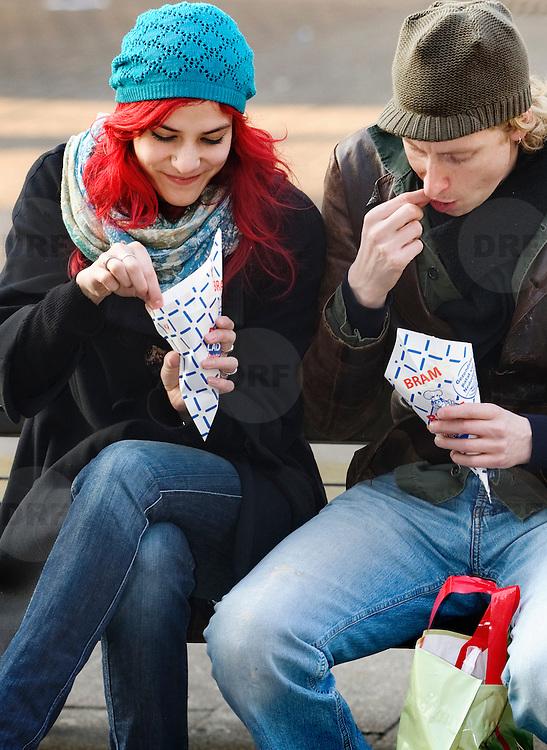 Nederland Rotterdam 18 februari 2008 20080218 .Een stel eet papat/ snackt op een bankje in de zon op Binnenwegplein in centrum Rotterdam ..'Vettax' goed middel tegen ongezond eten.Extra accijns op ongezonde levensmiddelen als drank, tabak en snacks, is een goede methode om consumenten gezonder te laten eten. Dat is een van de ideeën van de Raad voor de Volksgezondheid en Zorg (RVZ) om mensen meer verantwoordelijk te maken voor hun eigen gezondheid...Foto David Rozing