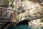 The source of the Buna river at the old Muslim monastery called the House of the Whirling Dervishes, below an impressive vertical cliff drop. A blonde woman standing on the balcony. The source of the Buna river and the house of the Whirling Dervishes, an old Muslim monastery, Blagaj. Federation Bosne i Hercegovine. Bosnia Herzegovina, Europe.