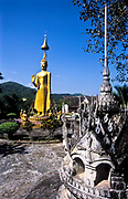 """As one enters the monastic complex, ones is welcomed by a shrine and a standing Buddha with a raised hand in a gesture of reassurance and blessing to visitors, The """"parasol"""" over his head indicates the supremacy of Buddhism. The central figure of the Manfeilang Monastery ( of the Dai denomination) is the White Pagoda  which lies on elevated ground on the banks of the Mekong river in south west Yunnan province.  Dai monasteries are built in the centre of a village or as in this case outside  on higher ground.<br /> <br /> Built in 1204, the Manfeilang monastery complex is in fact a cluster of nine pagodas or stupas, to enshrine what is purported to be the Buddha's footprint. The whole ensemble forms a fusion of Southeast Asian Buddhist style with typical Dai architecture. It is popular for Buddhist pilgrims from the surrounding region which attracts thousands during the Tan Ta Festival in late October early November each year.  In this region and in these Dai and Sino-Burmese monasteries, Theravada Buddhism is the religion that is practiced."""