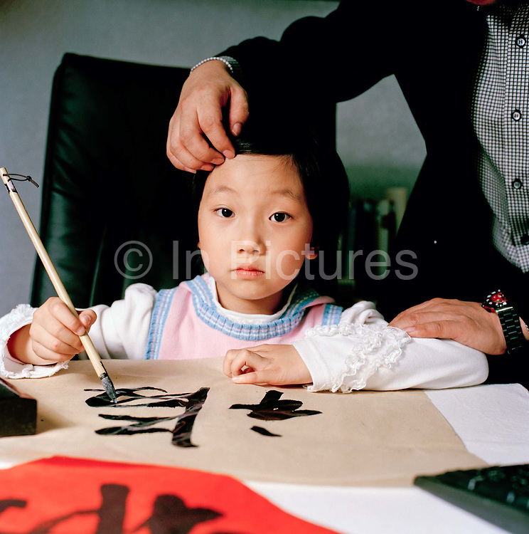 Wang Ying Chen, 7, at her calligraphy school in Beijing. Ying Chen is a gifted calligraphist and artist...Gao Wen Hong, 41, is CEO of a cosmetics company. Her husband, Wang Wei, also 41, is the director. They have one daughter, Wang YingChen, 7 who is top of the class at her primary school which has the best results in Beijing. Wen Hong says she prefers to have only one child so she can put all her resources into her. ..Its over thirty years (1978) since the Mao's Chinese government brought in the One Child Policy in a bid to control the world's biggest, growing population. It has been successful, in controlling growth, but has led to other problems. E.G. a gender in-balance with a projected 30 million to many boys babies; Labour shortages and a lack of care for the elderly.