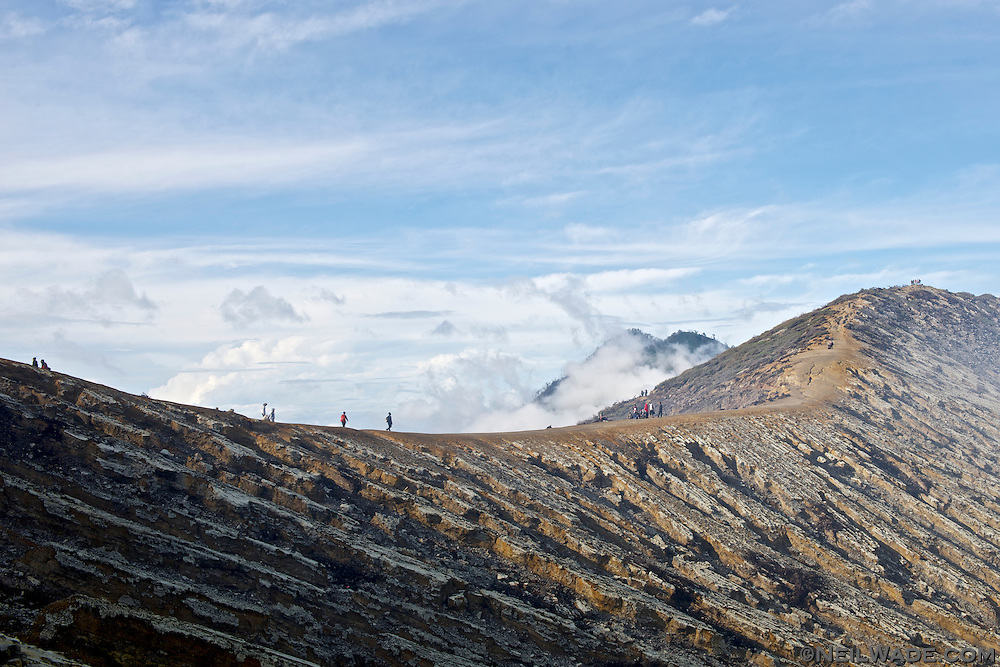 Tourists and workers walk along Mt. Ijen's crater rim.