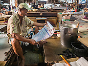 04 JANUARY 2016 - BANGKOK, THAILAND:        A baker in Bang Chak Market looks at a calendar before opening for the last time in Bang Chak Market on the day the market closed. The market closed January 4, 2016. The Bang Chak Market serves the community around Sois 91-97 on Sukhumvit Road in the Bangkok suburbs. About half of the market has been torn down. Bangkok city authorities put up notices in late November that the market would be closed by January 1, 2016 and redevelopment would start shortly after that. Market vendors said condominiums are being built on the land.   PHOTO BY JACK KURTZ
