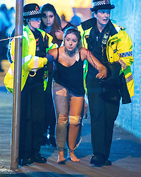 © Licensed to London News Pictures . FILE PICTURE DATED 22/05/2017 as Manchester prepares to mark a year since the Manchester Arena terror attack . Manchester, UK. EVE SENIOR (14, from Bradford) being assisted by police after being injured in the attack . Wounded people on Hunts Bank outside Victoria Station and the stairs leading to the Manchester Arena . Police and other emergency services are seen near the Manchester Arena after Salman Abedi murdered 22 and injured dozens more at an Ariana Grande concert at the Manchester Arena . Photo credit : Joel Goodman/LNP