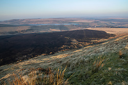 © Licensed to London News Pictures . 27/03/2020. Bolton, UK. GV of the scorched moorland damaged by the fire . Fire-fighters have worked to contain a large fire, reported to have been started by a barbecue, spread across Winter Hill, as people are told to stay at home during the covid 19 coronavirus outbreak . Photo credit: Joel Goodman/LNP