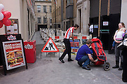 An employee from TGI Fridays sweeps the pavement outside as a family ready their buggy during a daytrip.
