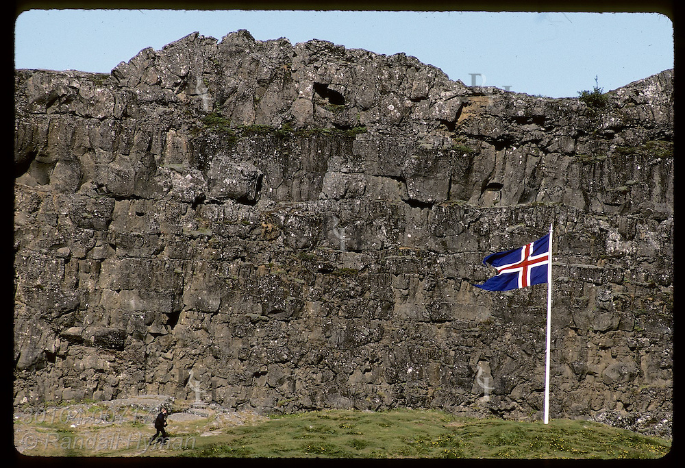 Flag flies by famous wall, Logberg, used by Vikings to cast voice to parliament crowd; Thingvellir Iceland