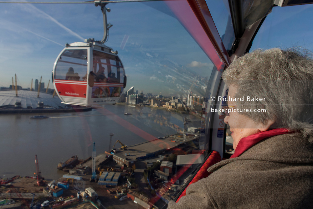 A lady passenger rides in a gondola on a journey over the River Thames on the Emirates Cable Car, from Royal Docks towards the Greenwich Peninsular. There are 34 gondolas, each with a maximum capacity of 10 passengers. The Emirates Air Line (also known as the Thames cable car) is a cable car link across the River Thames in London built with sponsorship from the airline Emirates. The service opened on 28 June 2012 and is operated by Transport for London. The service, announced in July 2010 and estimated to cost £60 million, comprises a 1-kilometre (0.62 mi) gondola line that crosses the Thames from the Greenwich Peninsula to the Royal Docks. ..