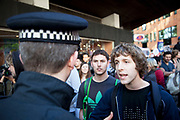 "Protesters make their point to lines of police blocking their exit. Occupy London protest, October 15th 2011. Protest spreads from the US with this demonstrations in London and other cities worldwide. The 'Occupy' movement is spreading via social media. After four weeks of focus on the Wall Street protest, the campaign against the global banking industry started in the UK this weekend, with the biggest event aiming to ""occupy"" the London Stock Exchange. The protests have been organised on social media pages that between them have picked up more than 15,000 followers. Campaigners gathered outside  at midday before marching the short distance to Paternoster Square, home of the Stock Exchange and other banks.It is one of a series of events planned around the UK as part of a global day of action, with 800-plus protests promised so far worldwide.Paternoster Square is a private development, giving police more powers to not allow protesters or activists inside."