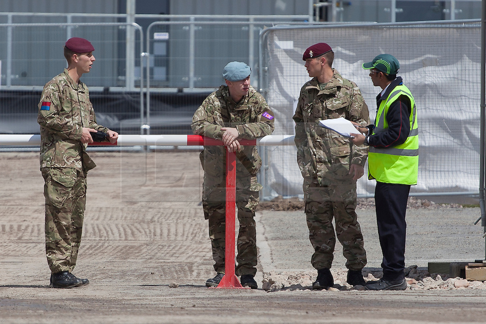 © licensed to London News Pictures. London, UK 19/07/2012. A group of soldiers talking to a G4S security guard at the military base in Hainault Country Park in Redbridge, east London. The base will accommodate 3,000 soldiers during the Olympics. Photo credit: Tolga Akmen/LNP
