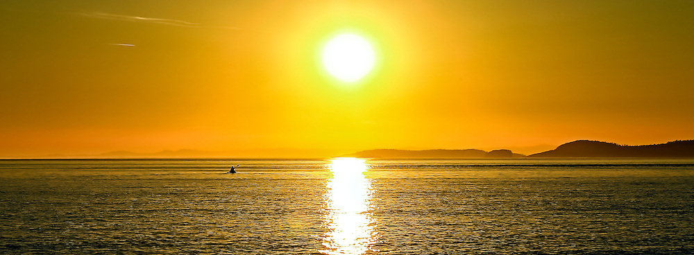 A solitary paddler takes his kayak out into the Pacific Ocean during a fiery golden sunset just off Whitby Island, Washington USA.