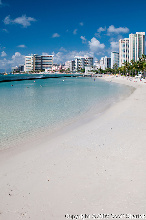 The sand of Waikiki Beach stretches out towards the towering hotels.