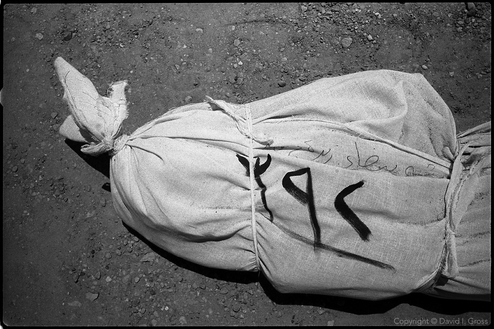 A body in a shroud at a mass grave near Al-Musayab, Iraq, with a code on it.