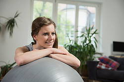 Close-up of a young woman taking a break after exercise in living room, Munich, Bavaria, Germany