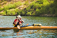 Kayaker takes photos from his wooden boat on The Colorado River, The Black Canyon, Nevada.