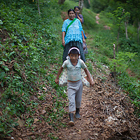 A family walks along a path in Concepción Actelá, the boy carries a baby wrapped in a sheet  with a headband called a 'mecapal'.