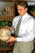 Lawyer age 27 referring to globe in office.  St Paul Minnesota USA