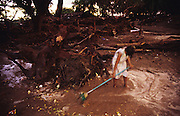 Central America, Honduras, Choluteca. Devastation in the aftermath of Hurricane Mitch. High winds and flooding. Soil erosion caused by deforestation. Girl attempts to sweep water from the site which was her home. Infrastructure destroyed.